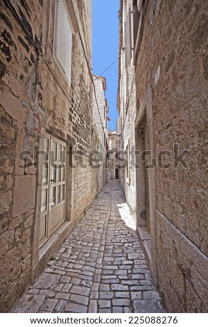Narrow cobbled street in Trogir center, antique Dalmatian city founded 4000 years ago. - stock photo