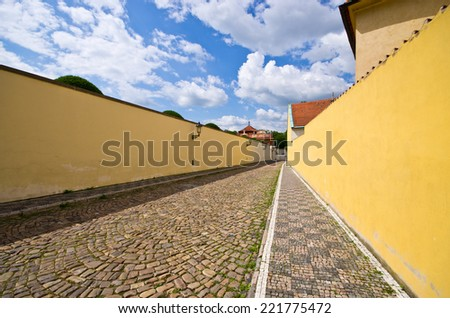 Narrow cobblestone street with wall - Prague, Czech Republic - stock photo
