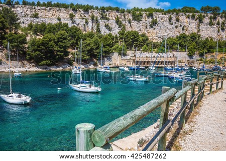 Narrow fjords between stony coast. White sailing yachts wait for the owners.  National Park Calanques on the Mediterranean coast - stock photo