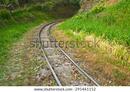 Narrow gauge railway tracks of Himalayan Mountain railway at Batasia loop in Darjeeling, India. - stock photo