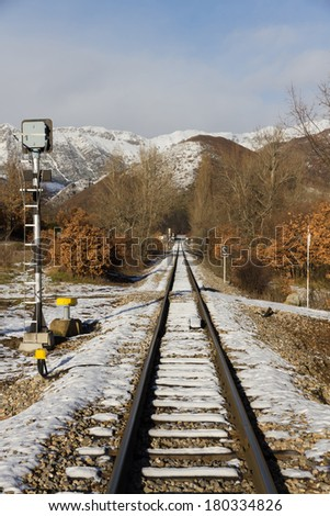Narrow Gauge Train via in snowy landscape with trees and mountains on both sides  - stock photo