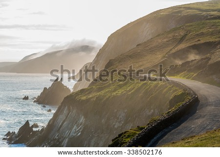 Narrow Irish coastal road in spring evening, just above the steep and dangerous cliffs. - stock photo