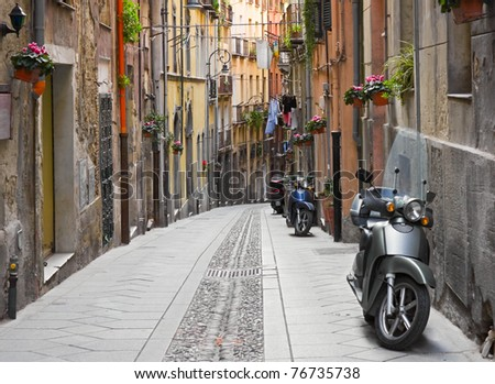 Narrow italian street with parked motorcycles, Cagliari, Sardinia. - stock photo