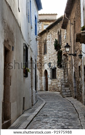 Narrow medieval street in Old Sigest town, historical resort-city close to Barcelona city, Spain - stock photo