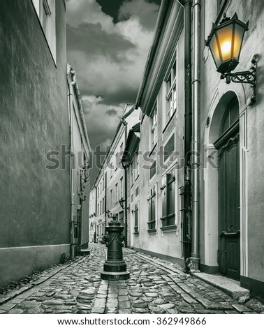 Narrow medieval street in the old Riga city, Latvia. The image was toned for inspiration of retro style - stock photo