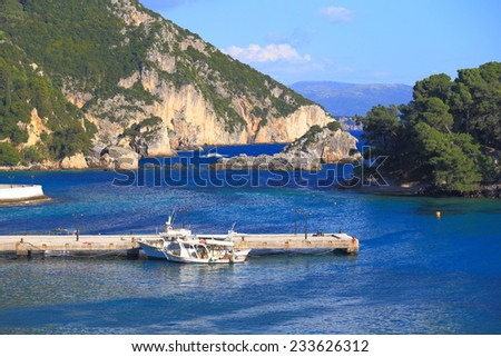 Narrow pier and traditional fishing boats in small harbor, Greece - stock photo