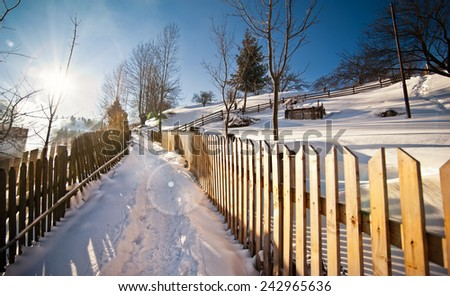 Narrow road covered by snow at countryside. Winter landscape with snowed trees, road and wooden fence. Cold winter day at countryside. Traditional Carpathian mountains village scenery, Romania - stock photo