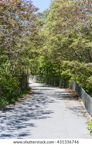 Narrow road from Pilgrim Monument in Provincetown, Massachusetts disappears around curve - stock photo
