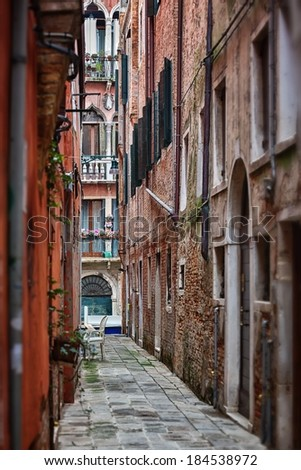 Narrow street among old colorful brick houses in Venice, Italy.