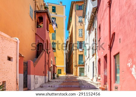 Narrow street among old colorful houses in Menton, France. - stock photo
