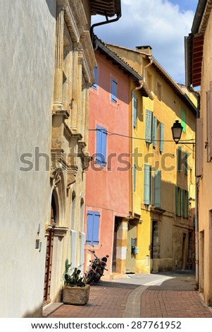 Narrow street and facades of colorful houses in Beautiful Medieval Village L'Isle sur la Sorgue. Provence, France - stock photo