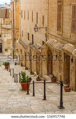 narrow street and stairs with old houses, Traditional Maltese architecture in Valletta, Malta - stock photo