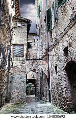 Narrow street between buildings with dramatic sky. (Siena. Tuscany, Italy)  - stock photo