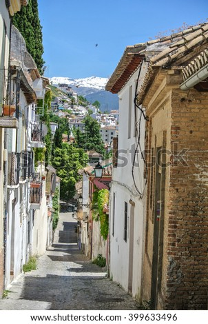 narrow street in an old mountain village in southern Europe with typical houses and colorful laundry - stock photo