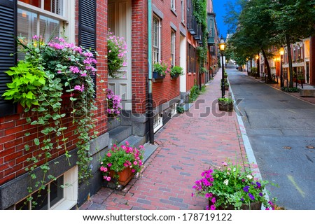 Narrow street in Beacon Hill, Boston. Flowers on window box, planters on brick sidewalk and old fashioned street lamps - stock photo