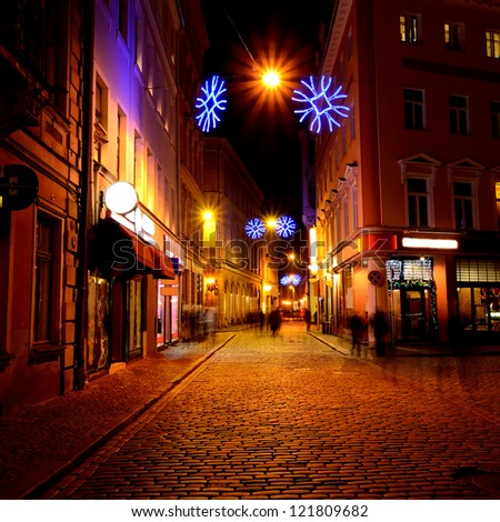 Narrow street in old Riga by night in Christmas time - stock photo