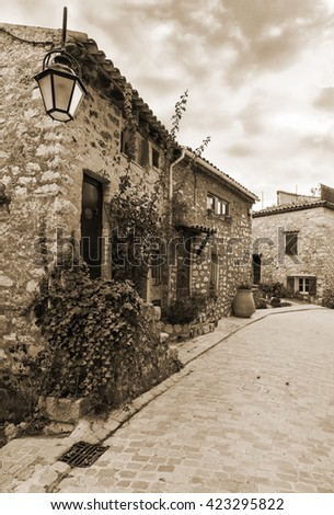 Narrow street in the old village Tourrettes-sur-Loup in France. The Old style sepia. - stock photo