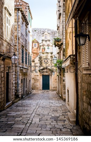 Narrow street inside Dubrovnik old town with church on the end. - stock photo