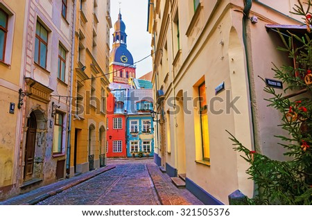Narrow street leading to the St. Peter church in Old Town of Riga, Latvia - stock photo