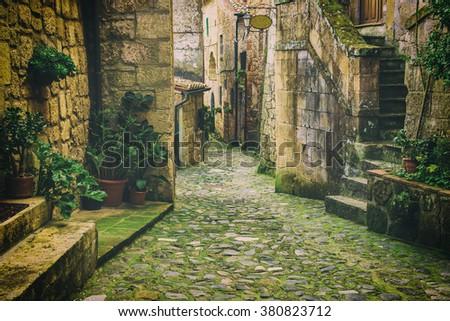 Narrow street of medieval tuff city Sorano with green plants and cobblestone, travel Italy vintage  background - stock photo