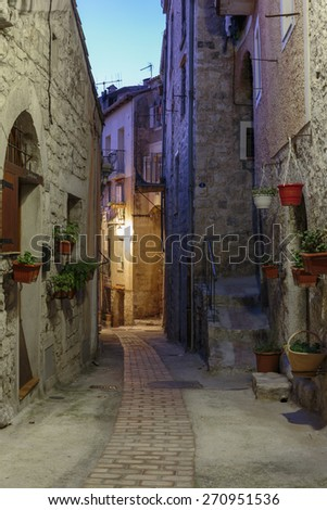 Narrow street with flowers in the old town Peille in France. Night view - stock photo
