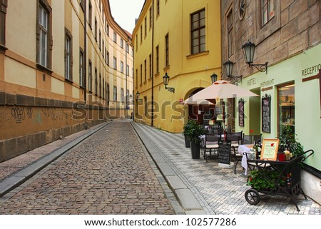 Narrow street with small hotel and outdoor restaurant in historic part of Prague, Czech Republic. - stock photo