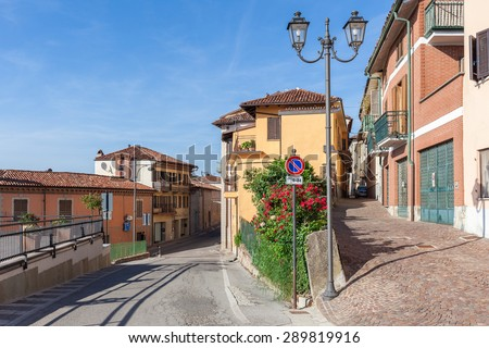 Narrow streets and lamppost among colorful houses in town of La Morra in Piedmont, Northern Italy. - stock photo