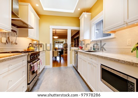 Narrow white and yellow kitchen with skylight and grey floor. - stock photo