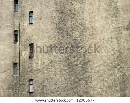 Narrow windows on the blank wall of old house