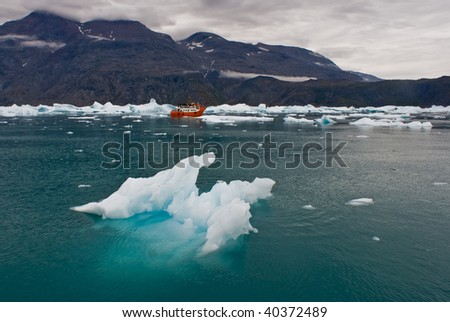 Narsarsuaq Icefjord, Greenland. Iceberg and Icy waters with a small red boat in the background. - stock photo
