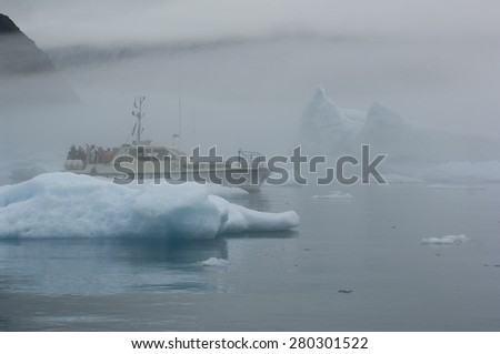 NARSUSUAQ/GREENLAND AUGUST 2007 - The blue icebergs of Narsusuaq Fjord in Greenland and a tour boat  - stock photo