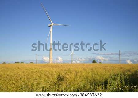 NARVA, ESTONIA - AUGUST 01, 2015: Two wind power generator on rapeseed field August evening