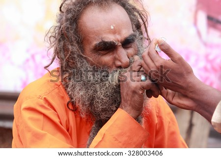 NASHIK - SEP 17:An unidentified Sadhu smoke chillum as he participates in the event Maha Kumbh Mela on September 17, 2015 in Nashik, India.Kumbhmela is a Hindu religious event gathered by millions. - stock photo