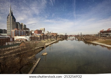 NASHVILLE, TENNESSEE-FEBRUARY 4, 2015:  The skyline of Nashville spans the Cumberland River.  This image has a texture overlay for a vintage feel. - stock photo