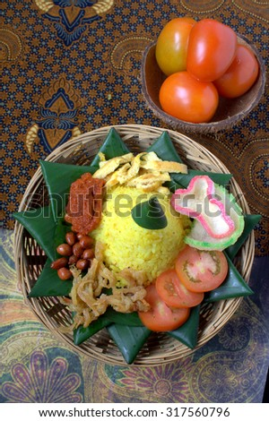Nasi kuning personal serving, surrounded with rich Indonesian dishes. Nasi kuning is famous food in Indonesia - stock photo