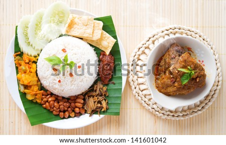 Nasi lemak is traditional malaysia spicy rice dish, fresh cooked with hot steam. Served with belacan, ikan bilis, acar, peanuts and cucumber. Decoration setup, malaysian cuisine. - stock photo