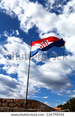 National flag of Croatia is waving against blue cloudy sky in sunlight