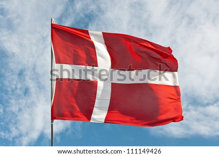 National flag of denmark flying in the wind against a summer sky - stock photo