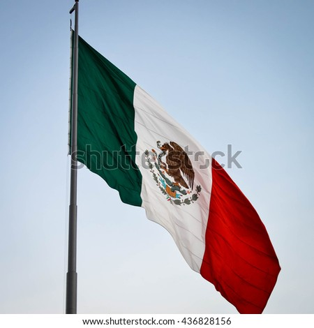 National flag of Mexico waving over Zocalo square in Mexico city with the blue sky background - stock photo