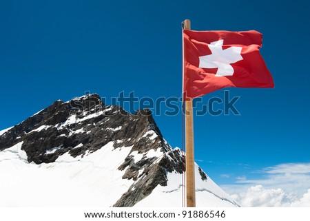 National Flag of Switzerland with the Jungfrau mountain peak - stock photo