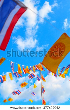 National flags and Wheel of Dhamma 's flags on string and blue sky at Thailand
