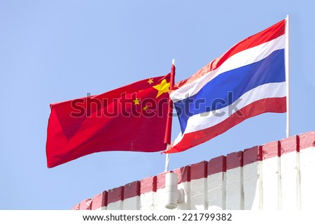 national flags of China and Thailand waving on top of building,