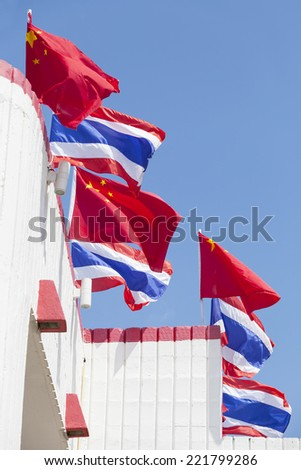 national flags of Thailand and China waving on top of building,