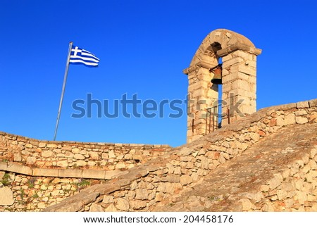 National Greek flag on a mast and bell tower on the walls of Palamidi fortress, Nafplio, Greece - stock photo