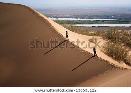 National park Altyn Emel. Kazakhstan. Two people on the top of a sand dune