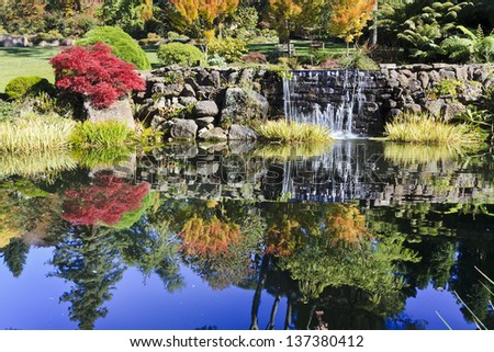 national park autumn colours reflection in water pond with blue sky and streaming waterfall red yellow leaves sunny day - stock photo