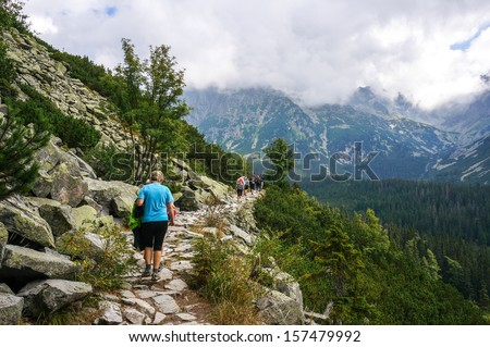 NATIONAL PARK HIGH TATRA, SLOVAKIA - CIRCA AUGUST 2013: People hiking in line on the path to the summit of Rysy circa August 2013