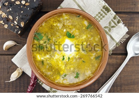 National ukrainian and russian soup borsch with sour cream in ceramic bowl with black bread on wooden table. Top view. - stock photo