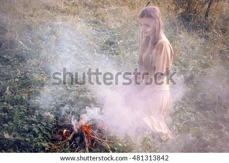 Native american indian girl performing shaman ritual near campfire & smoke