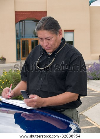 Native American man dialing a number on his cell phone - stock photo